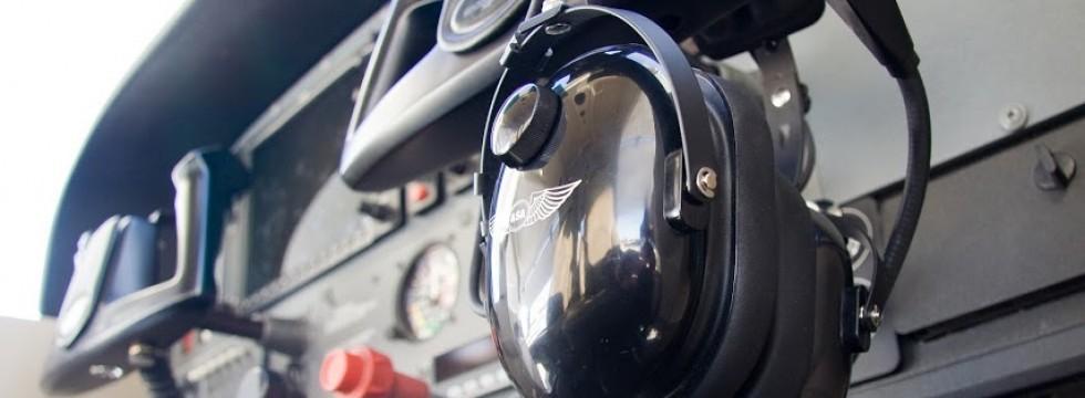 Auriculares de piloto colgados en el panel de la cabina